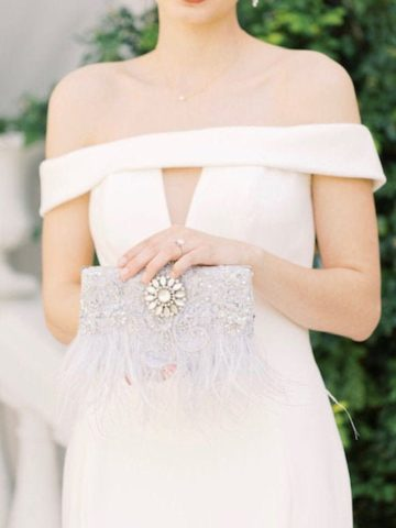 bride holding a feathered clutch