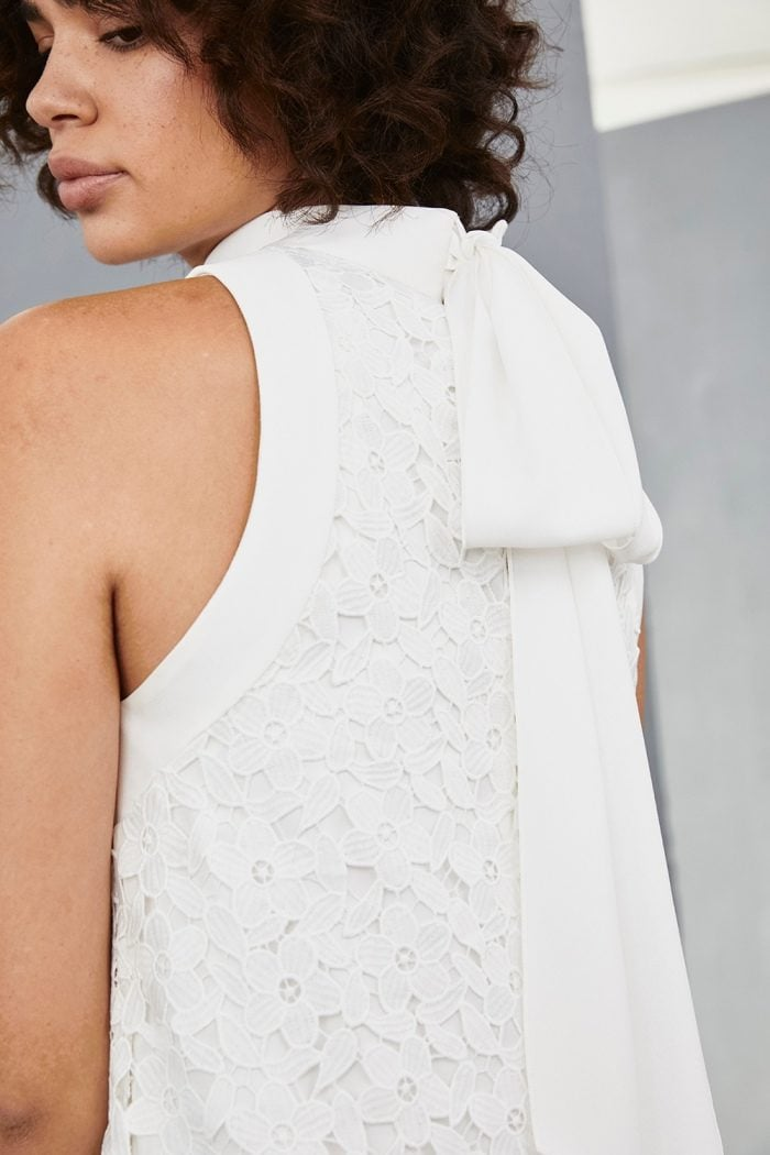 Bow tie detail on white lace mini dress