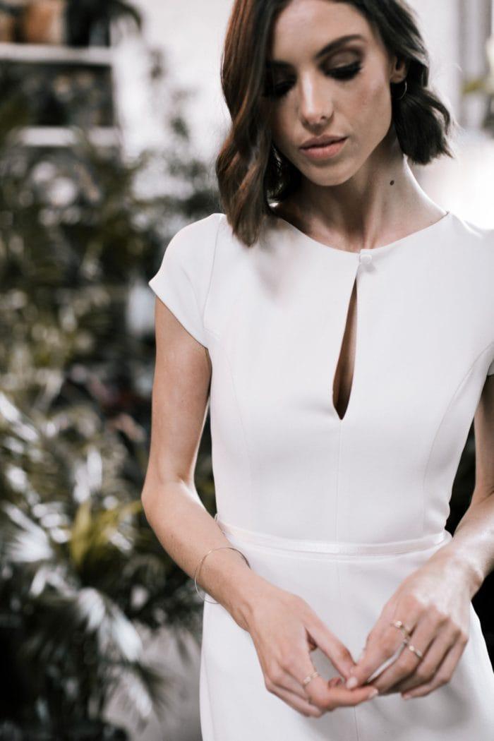 Neck detail of cap sleeve wedding dress with center split neckline | Clarissa gown