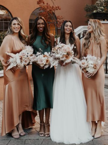 3 women in satin bridesmaid dresses in several colors and a bride