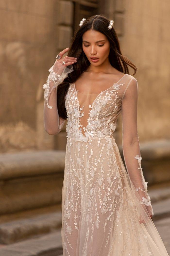 Long sleeve sheer embellished designer bridal gown with plunge neckline