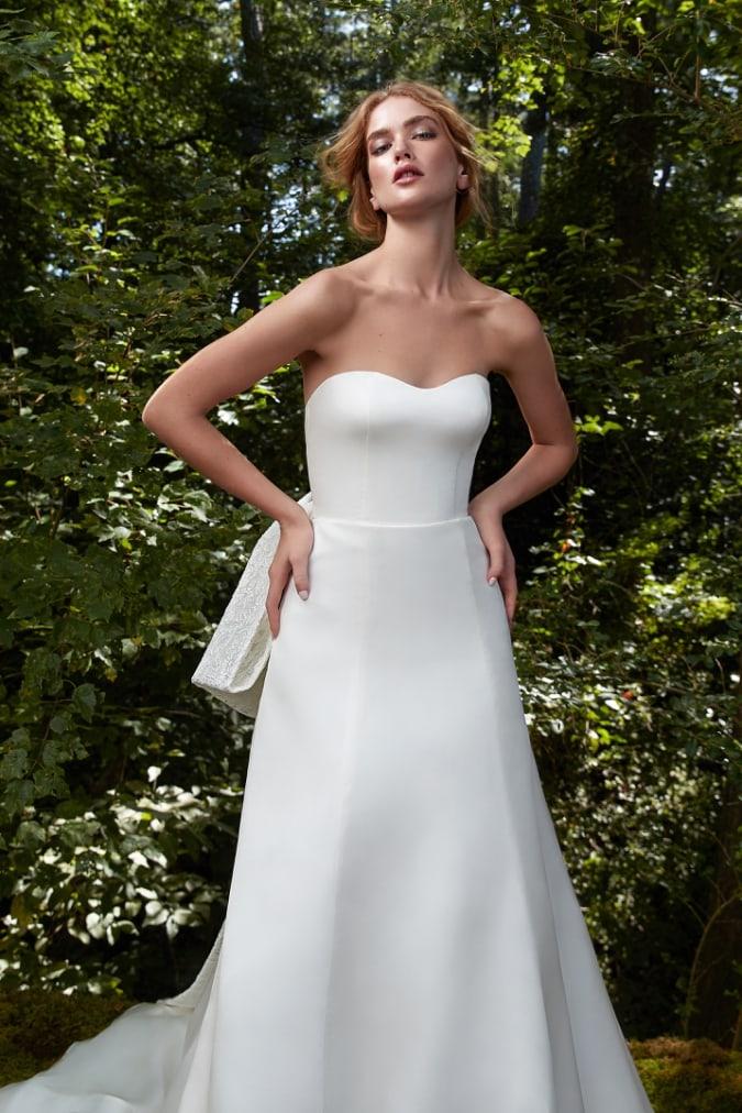 Strapless wedding dress set against green background