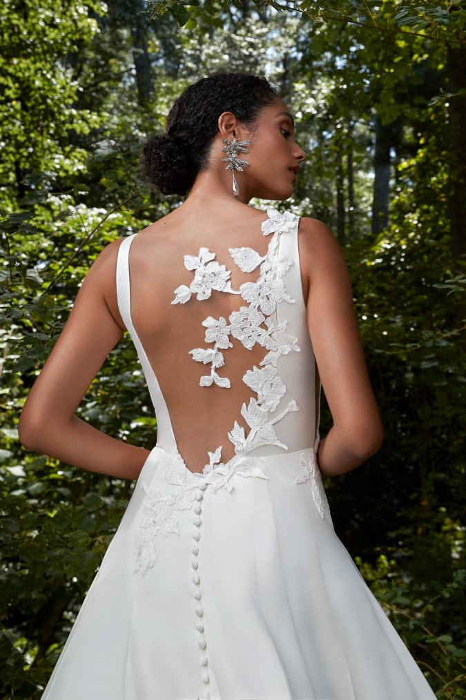 Bridal gown with floral applique details on the back designed by Anne Barge