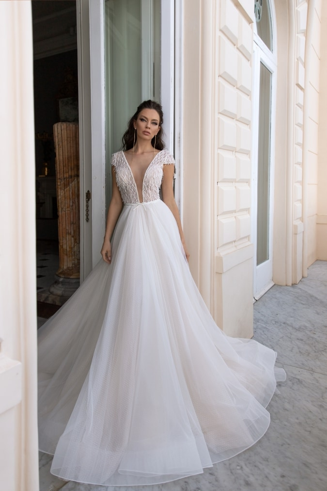Cap sleeve ivory wedding dress with plunging neckline worn by a model