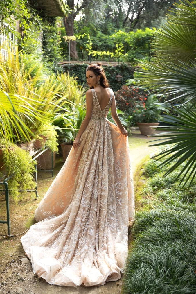 Neutral lace wedding dress shown against a garden