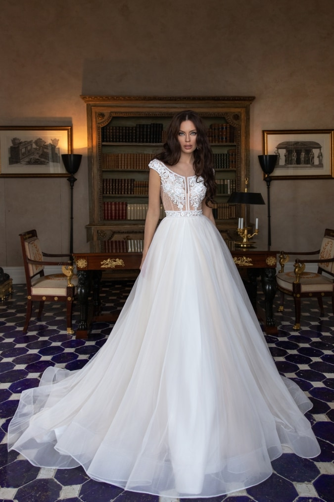 Cap sleeve lace top wedding dress worn by a model