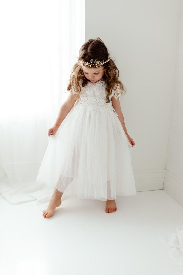 Young flower girl in a white dress
