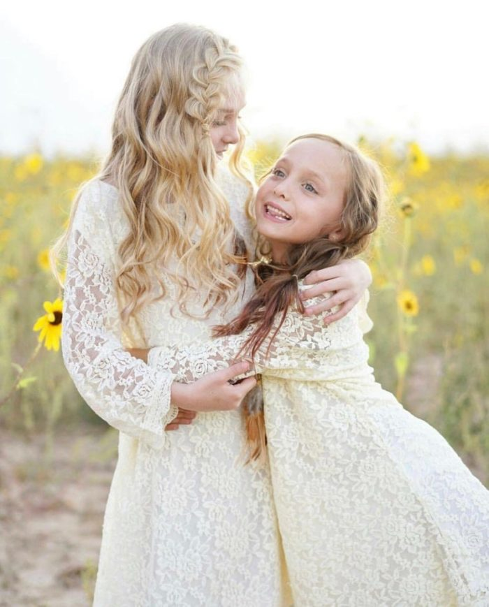 Two gilrs wearing white lace dresses and in a flower field